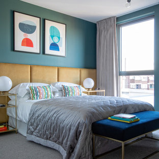 This is an example of a contemporary grey and brown bedroom in London with blue walls, carpet and grey floors.