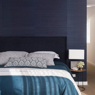 Design ideas for a mid-sized beach style master bedroom in Sydney with blue walls, carpet and brown floor.
