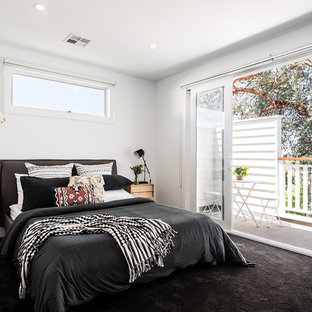 Mid-sized contemporary bedroom in Melbourne with white walls, carpet and black floor.