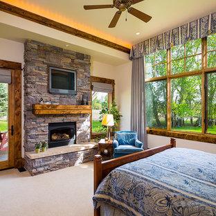 Ispirazione per una grande camera matrimoniale american style con pareti bianche, moquette, camino classico e cornice del camino in pietra