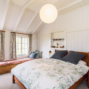 Inspiration for a country master bedroom in Hobart with white walls, carpet and a stone fireplace surround.