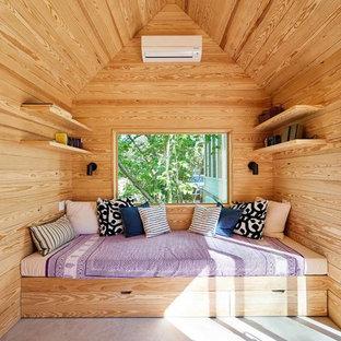 Diseño de habitación de invitados actual, sin chimenea, con paredes beige, suelo de cemento y suelo gris