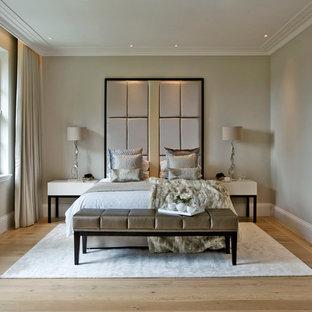 Transitional medium tone wood floor bedroom photo in London with beige walls