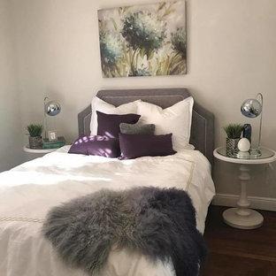 Imagen de habitación de invitados moderna, grande, con paredes grises, suelo de madera clara, chimenea tradicional y marco de chimenea de ladrillo