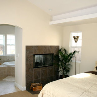 This is an example of a mid-sized contemporary master bedroom in Los Angeles with porcelain floors, a two-sided fireplace and a tile fireplace surround.