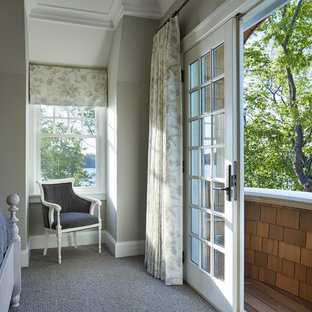 Esempio di una camera degli ospiti costiera di medie dimensioni con moquette, camino classico, cornice del camino in pietra, pareti grigie e pavimento marrone