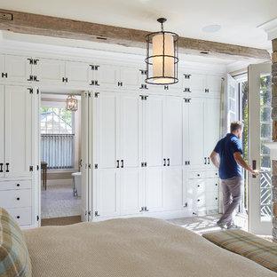 На фото: большая хозяйская спальня в морском стиле с ковровым покрытием, камином, коричневым полом и бежевыми стенами с