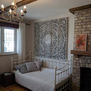 Foto de habitación de invitados ecléctica con paredes grises, suelo de madera clara, estufa de leña, marco de chimenea de ladrillo y suelo beige