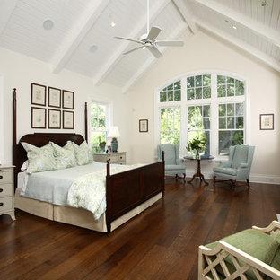 Modelo de dormitorio tradicional con paredes beige, suelo de madera oscura, chimenea tradicional y marco de chimenea de baldosas y/o azulejos