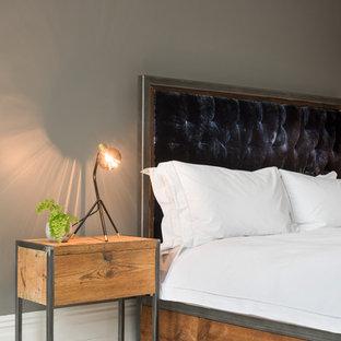 Esempio di una grande camera matrimoniale minimalista con pareti grigie, pavimento in legno verniciato, stufa a legna, cornice del camino in legno e pavimento bianco