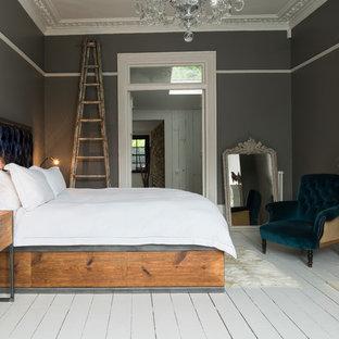 Foto de dormitorio principal, moderno, grande, con paredes grises, suelo de madera pintada, estufa de leña, marco de chimenea de madera y suelo blanco