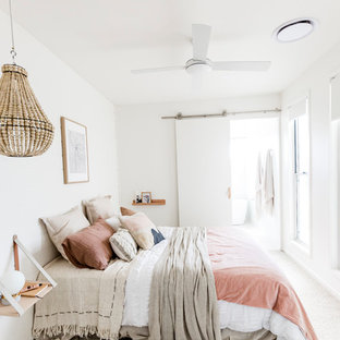 This is an example of a beach style master bedroom in Sunshine Coast with white walls, carpet and beige floor.