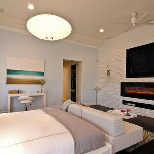 Imagen de dormitorio principal, tradicional renovado, grande, con paredes azules, suelo de madera oscura, chimenea lineal y marco de chimenea de piedra