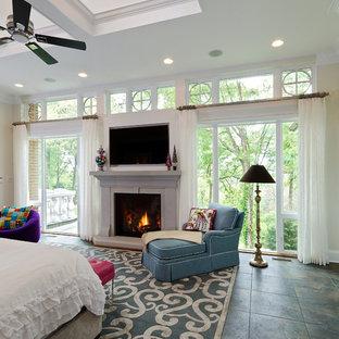 Imagen de dormitorio principal, clásico renovado, grande, con paredes blancas, suelo de pizarra, chimenea tradicional y marco de chimenea de piedra