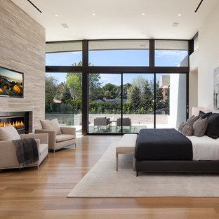 Idée de décoration pour une très grand chambre parentale design avec une cheminée ribbon, un manteau de cheminée en pierre, un mur blanc, un sol en bois clair et un sol marron.