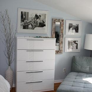 Modelo de dormitorio principal, minimalista, de tamaño medio, sin chimenea, con paredes azules y suelo de madera clara