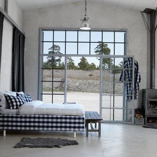 Ejemplo de dormitorio principal, minimalista, extra grande, con paredes blancas, suelo de cemento, estufa de leña y marco de chimenea de metal