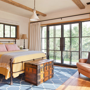 Inspiration for a rustic bedroom in Other with white walls, medium hardwood flooring and orange floors.