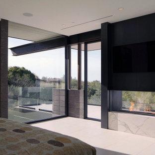 Imagen de dormitorio de estilo americano, grande, con paredes blancas, suelo de baldosas de porcelana, chimenea de doble cara, marco de chimenea de metal y suelo blanco