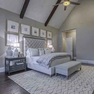 Modelo de dormitorio principal, clásico renovado, grande, con paredes grises, suelo de madera oscura, chimenea de doble cara y marco de chimenea de piedra