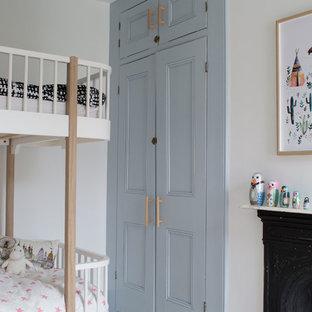 Imagen de dormitorio escandinavo, de tamaño medio, con paredes blancas, suelo de madera pintada, chimenea tradicional y marco de chimenea de metal