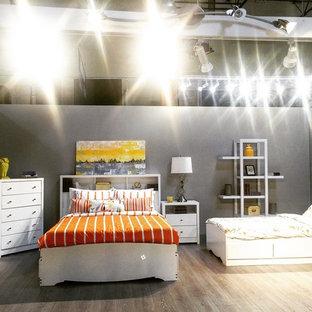 Modelo de dormitorio tipo loft, tropical, grande, con paredes blancas y suelo laminado