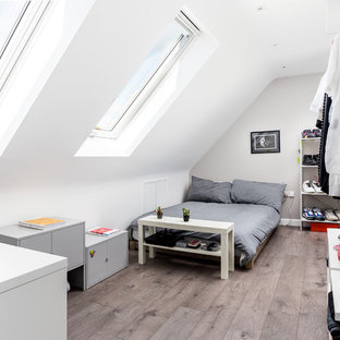 Design ideas for a medium sized modern mezzanine bedroom in Sussex with beige walls, laminate floors, no fireplace and brown floors.