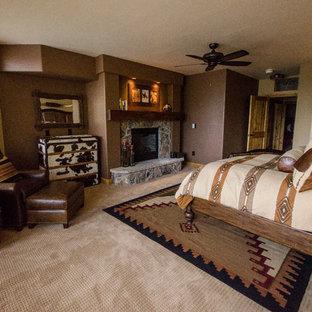 デンバーの広いサンタフェスタイルのおしゃれな主寝室 (ベージュの壁、カーペット敷き、標準型暖炉、石材の暖炉まわり) のレイアウト