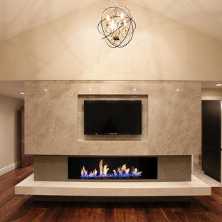 Imagen de dormitorio principal, actual, extra grande, con paredes beige, suelo de madera oscura, chimenea lineal y marco de chimenea de yeso