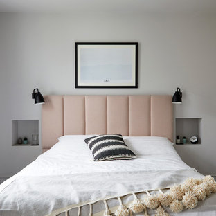 Large scandi master bedroom in London with white walls, carpet and beige floors.