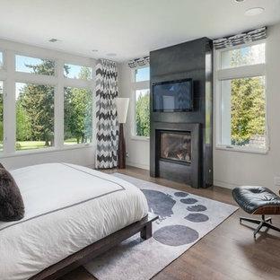 Ejemplo de dormitorio principal, actual, de tamaño medio, con paredes blancas, suelo de madera oscura, chimenea tradicional y marco de chimenea de hormigón
