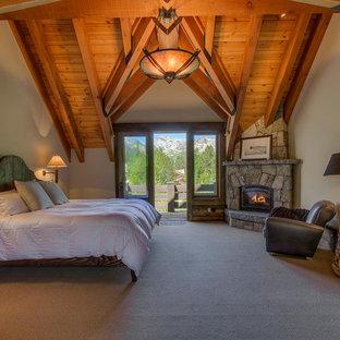 Diseño de dormitorio rústico, extra grande, con paredes blancas, moqueta, chimenea de esquina, marco de chimenea de piedra y suelo beige