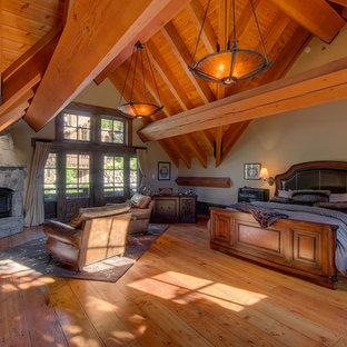 Aménagement d'une très grand chambre montagne avec un mur blanc, un sol en bois brun, une cheminée d'angle, un manteau de cheminée en pierre et un sol marron.