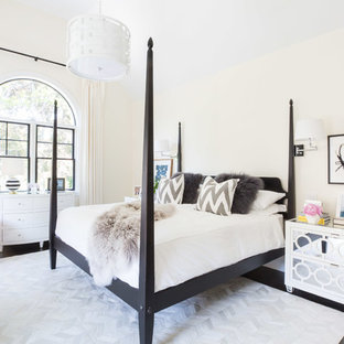 This is an example of a traditional bedroom in New York with beige walls and dark hardwood flooring.