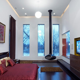 Photo of an expansive modern loft-style bedroom in Chicago with beige walls, dark hardwood floors and a hanging fireplace.