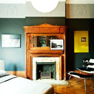 Immagine di una camera da letto minimal con pareti nere, pavimento in legno massello medio e camino classico