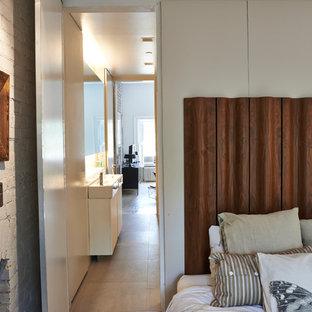Foto de dormitorio principal, actual, pequeño, con suelo de madera pintada, chimenea tradicional, marco de chimenea de ladrillo, paredes beige y suelo beige