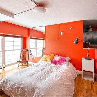 Modelo de dormitorio tipo loft con parades naranjas y suelo de madera en tonos medios
