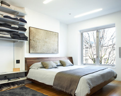 inspiration for a mid sized contemporary medium tone wood floor and brown floor bedroom remodel