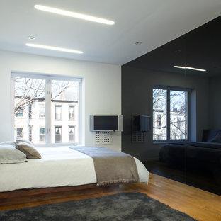 Imagen de dormitorio tipo loft, minimalista, de tamaño medio, con paredes blancas, suelo de madera en tonos medios y suelo verde