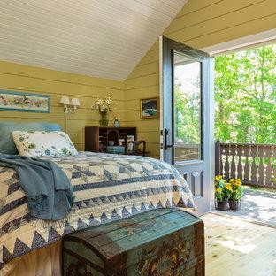 Imagen de dormitorio principal, campestre, de tamaño medio, sin chimenea, con paredes amarillas, suelo de madera clara y suelo marrón