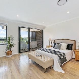 Modern bedroom in Sydney with beige walls, medium hardwood floors and brown floor.