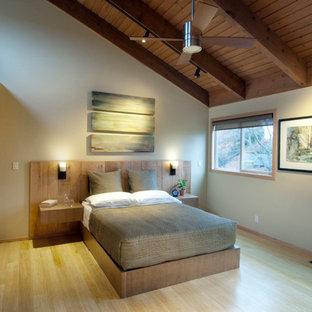 Ejemplo de dormitorio principal, contemporáneo, de tamaño medio, con paredes beige y suelo de bambú