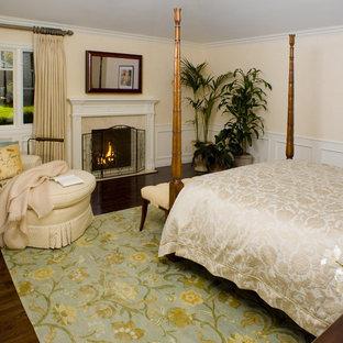 Inspiration för ett vintage sovrum, med beige väggar, mörkt trägolv och en standard öppen spis