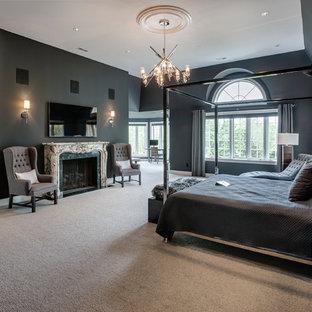 Ispirazione per una camera matrimoniale classica con pareti nere, moquette e camino classico