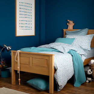 Modelo de dormitorio contemporáneo con suelo de madera en tonos medios