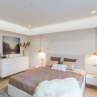 This is an example of a medium sized contemporary master bedroom in Manchester with white walls, light hardwood flooring and beige floors.