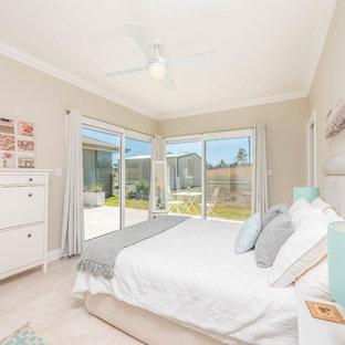Beach style guest bedroom in Sydney with beige walls and beige floor.