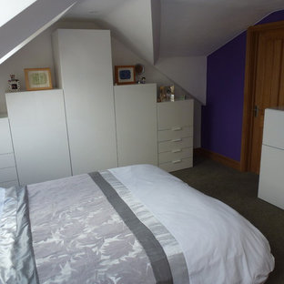 Design ideas for a mid-sized midcentury loft-style bedroom in Gloucestershire with purple walls, carpet and no fireplace.