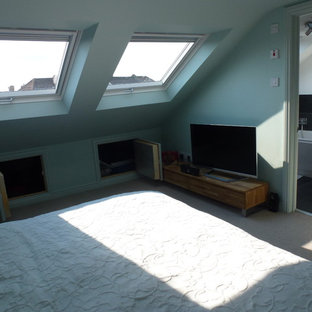 Inspiration for a mid-sized modern loft-style bedroom in Gloucestershire with blue walls, carpet and no fireplace.